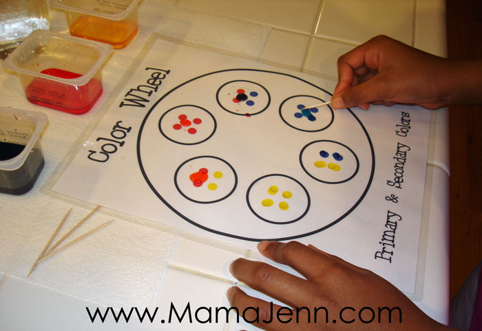 hands mixing food coloring on printable color wheel activity page using a toothpick