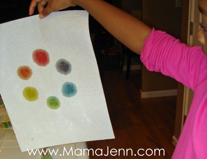 hands hold up a secondary color wheel on a paper towel