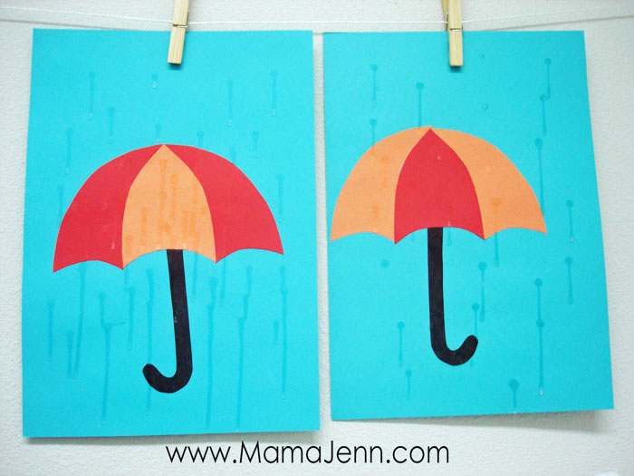 blue construction paper with red and orange umbrella craft with dry glue as raindrops