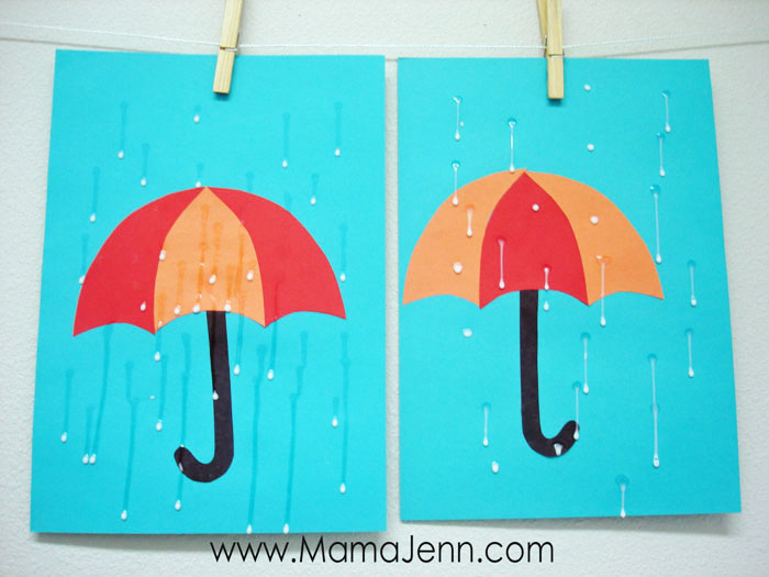 blue construction paper with red and orange umbrella craft with wet glue as raindrops