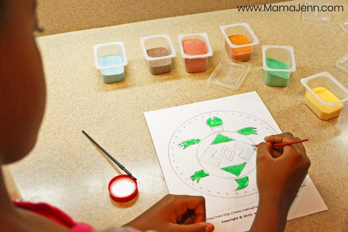 child doing an art project using colored sand