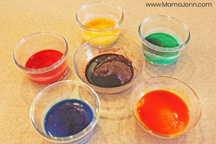 six bowls with colored sand being made in them
