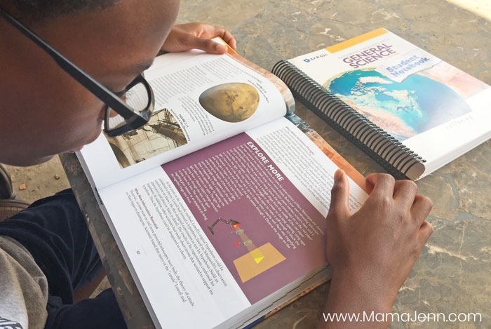 boy reading Apologia General Science textbook