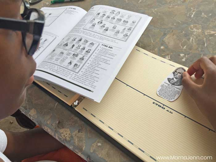 boy adding timeline figure to Home School in the Woods Record of History timeline notebook