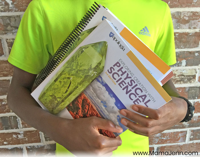boy holding Apologia Physical Science Student Notebook and textbook