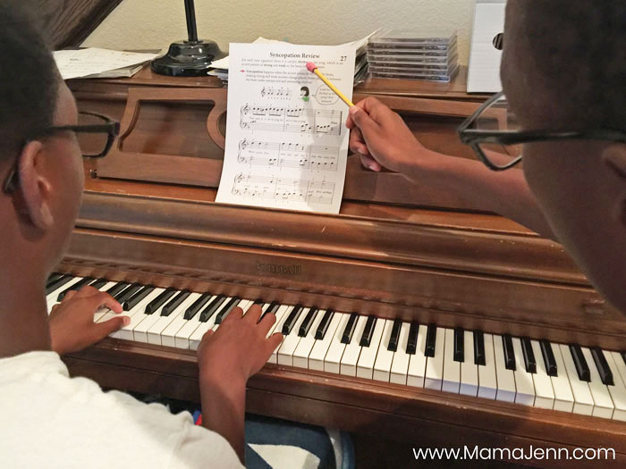 a boy teaching piano lessons to another boy
